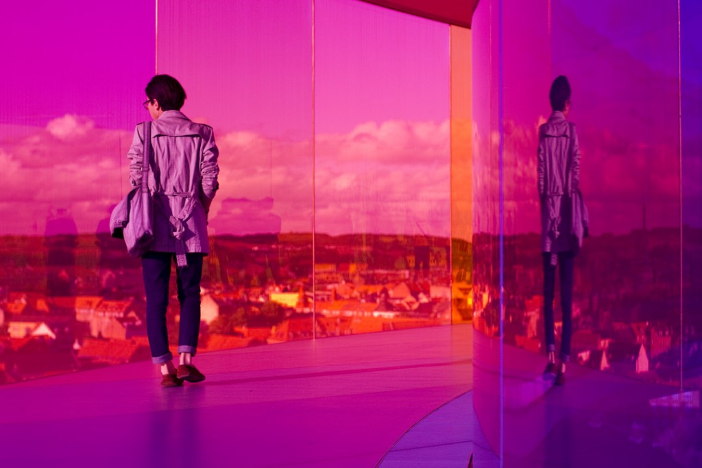 A man walking through Olafur Eliasson's Your Rainbow Panorama at the ARoS Museum. Photo by Erin Brown.