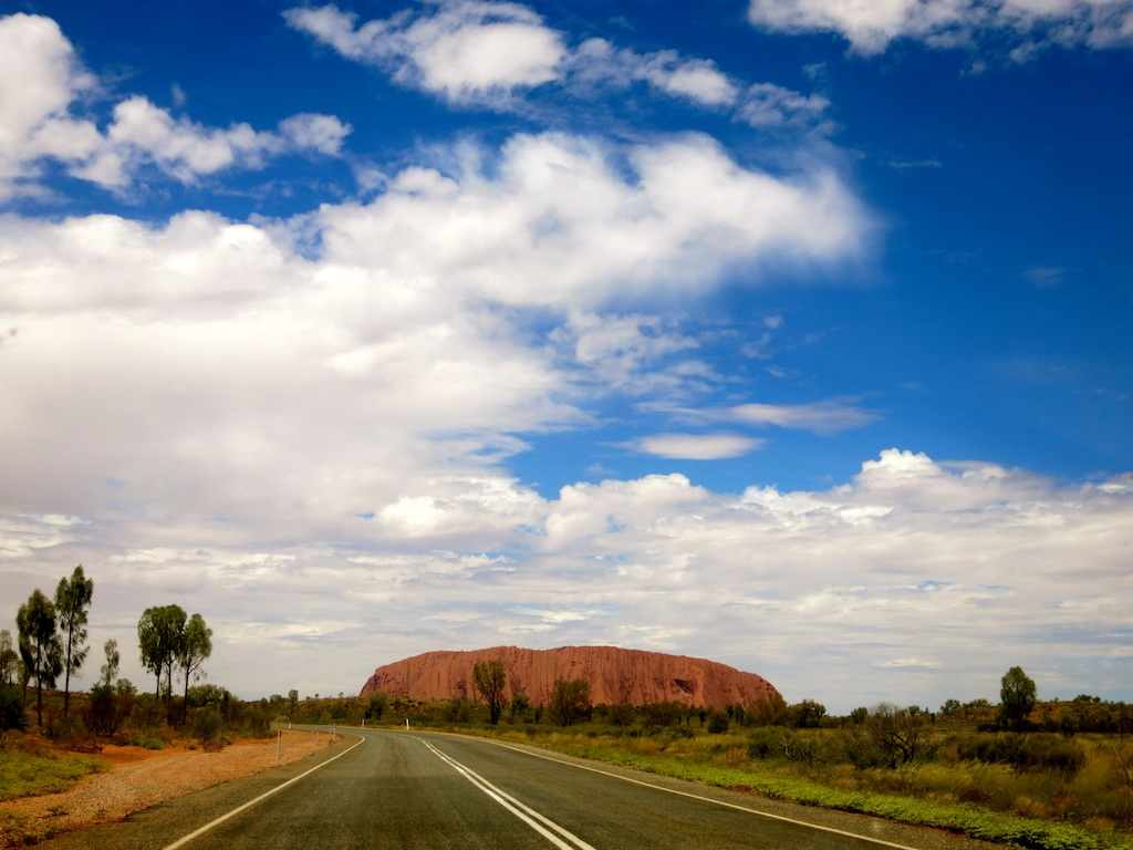 Uluru set against the Australian outback.