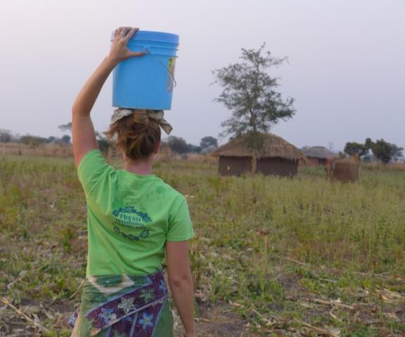 A girl carries a bucket through the fields.