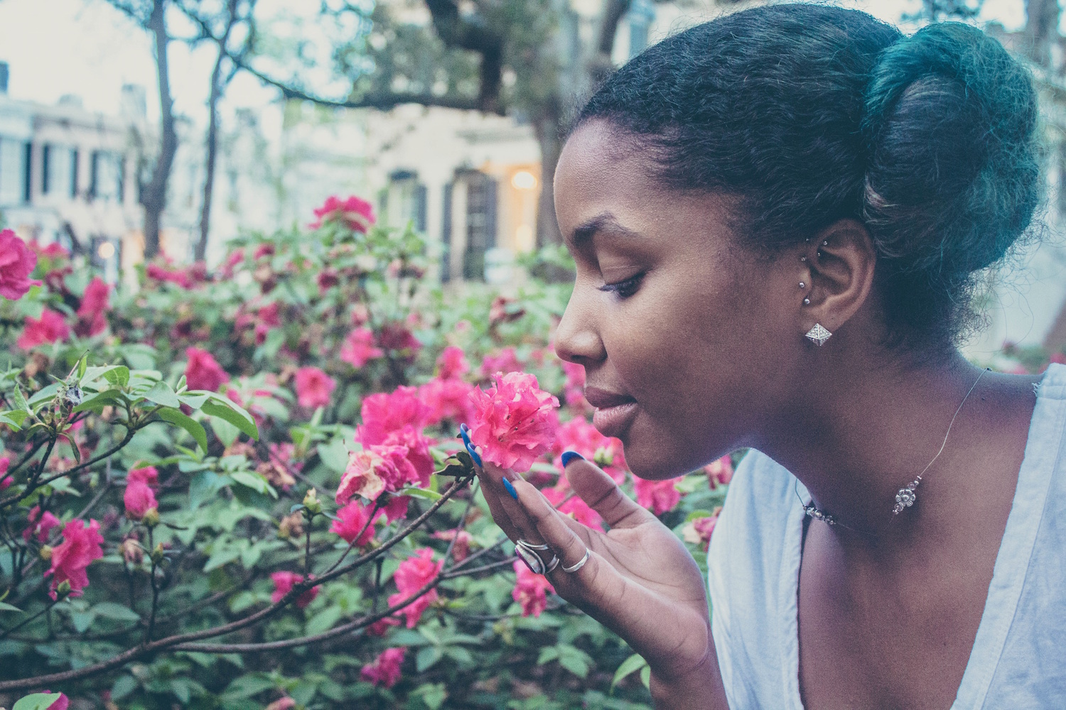 Close up image of a Black woman smelling a pink flower