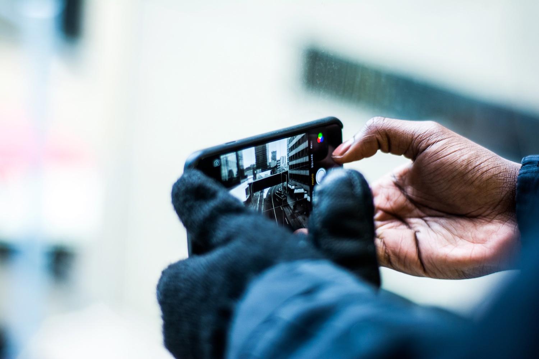 Black woman taking a phone photo