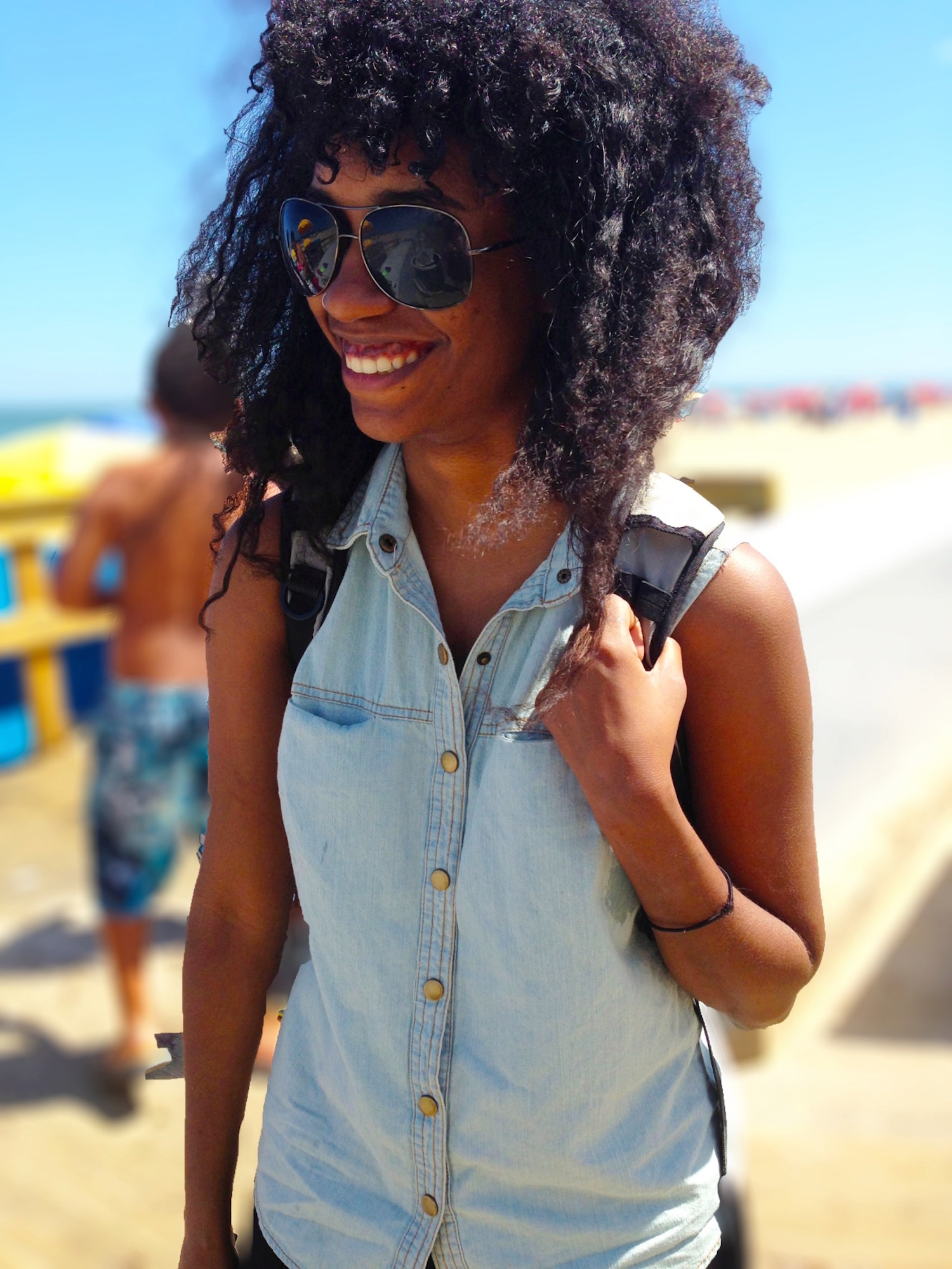 Solo travel for Black women - a smiling Black woman with a backpack on