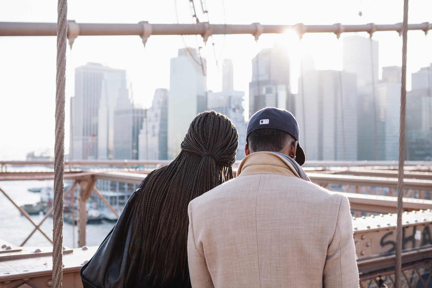 A Black woman and a Black man facing toward the city