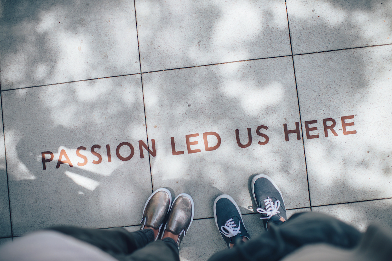 "Two people standing on a sidewalk over the words"" Passion led us here"""