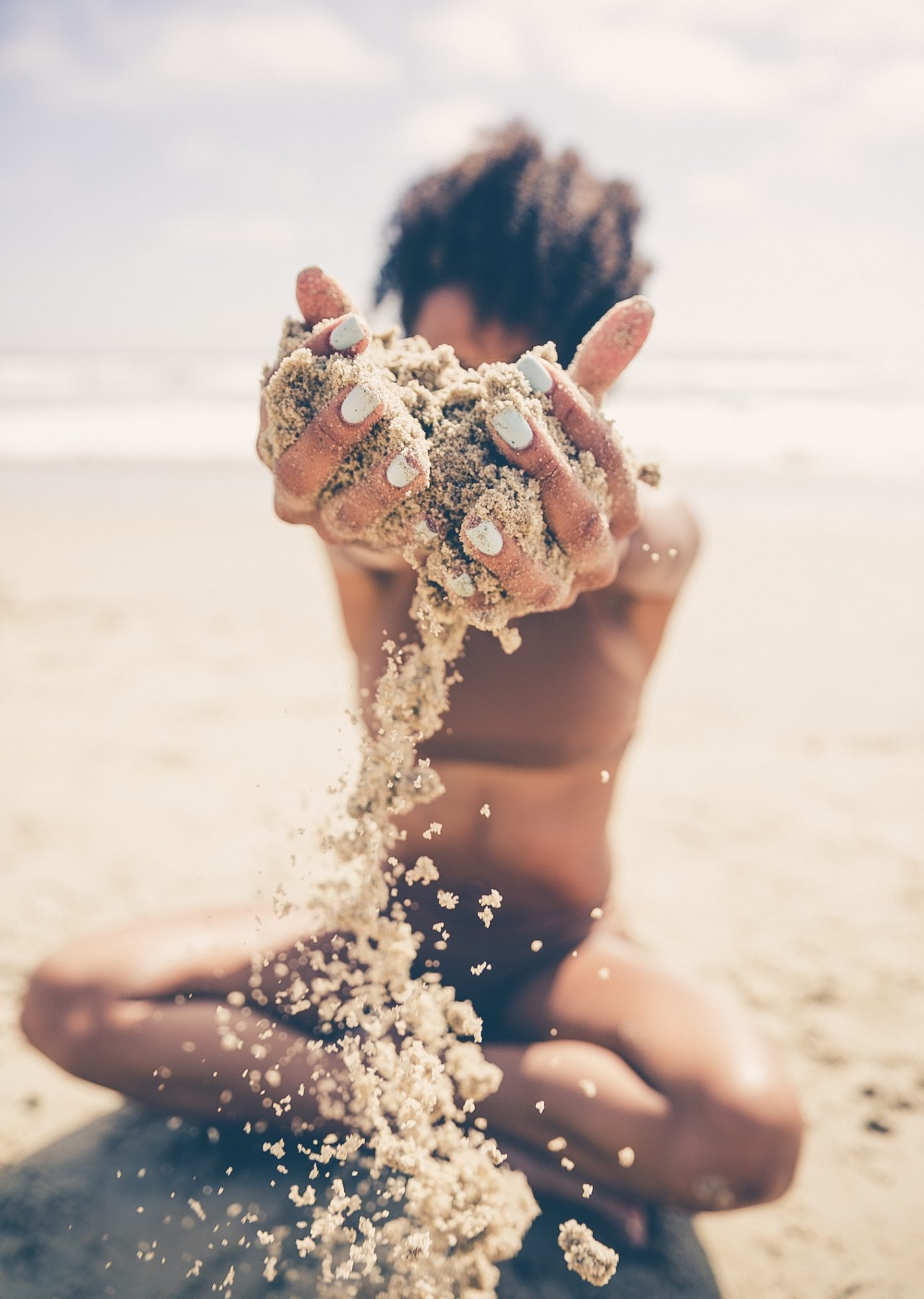 Black woman with sand falling from her hands