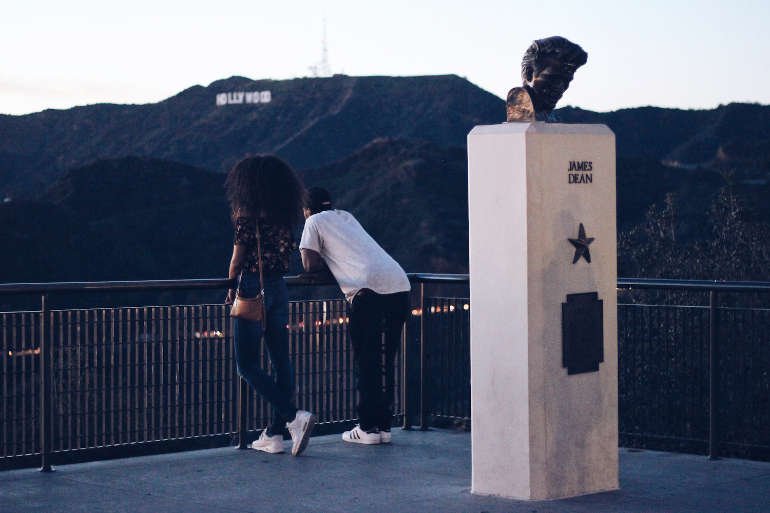 Black woman and Black man facing the Hollywood sign next to the James Dean monument