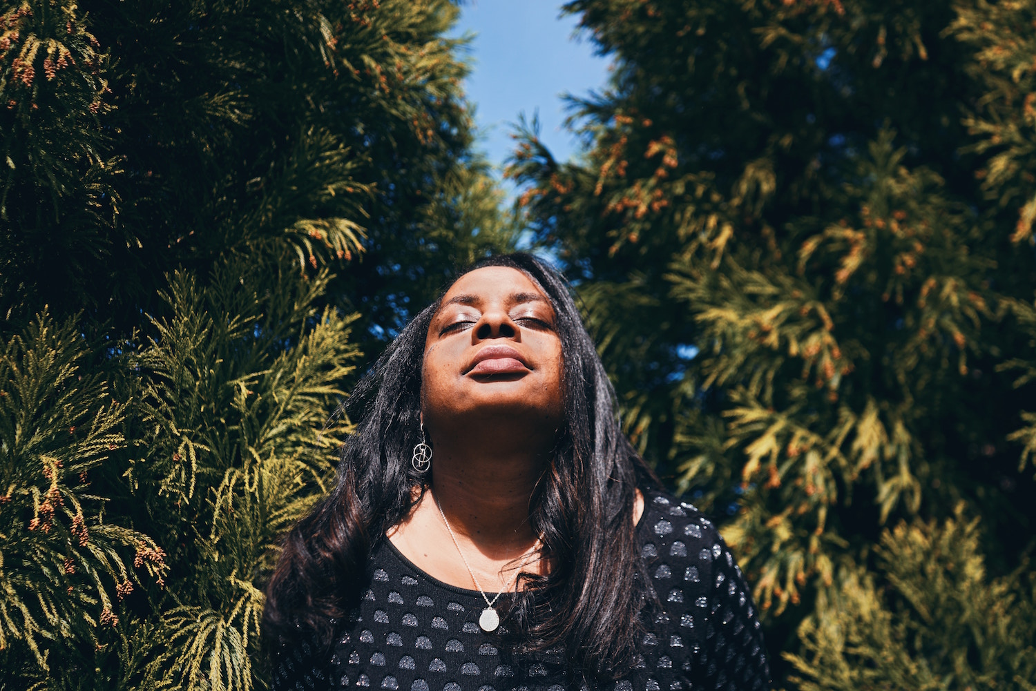 Black woman with her face lifted up toward the sun