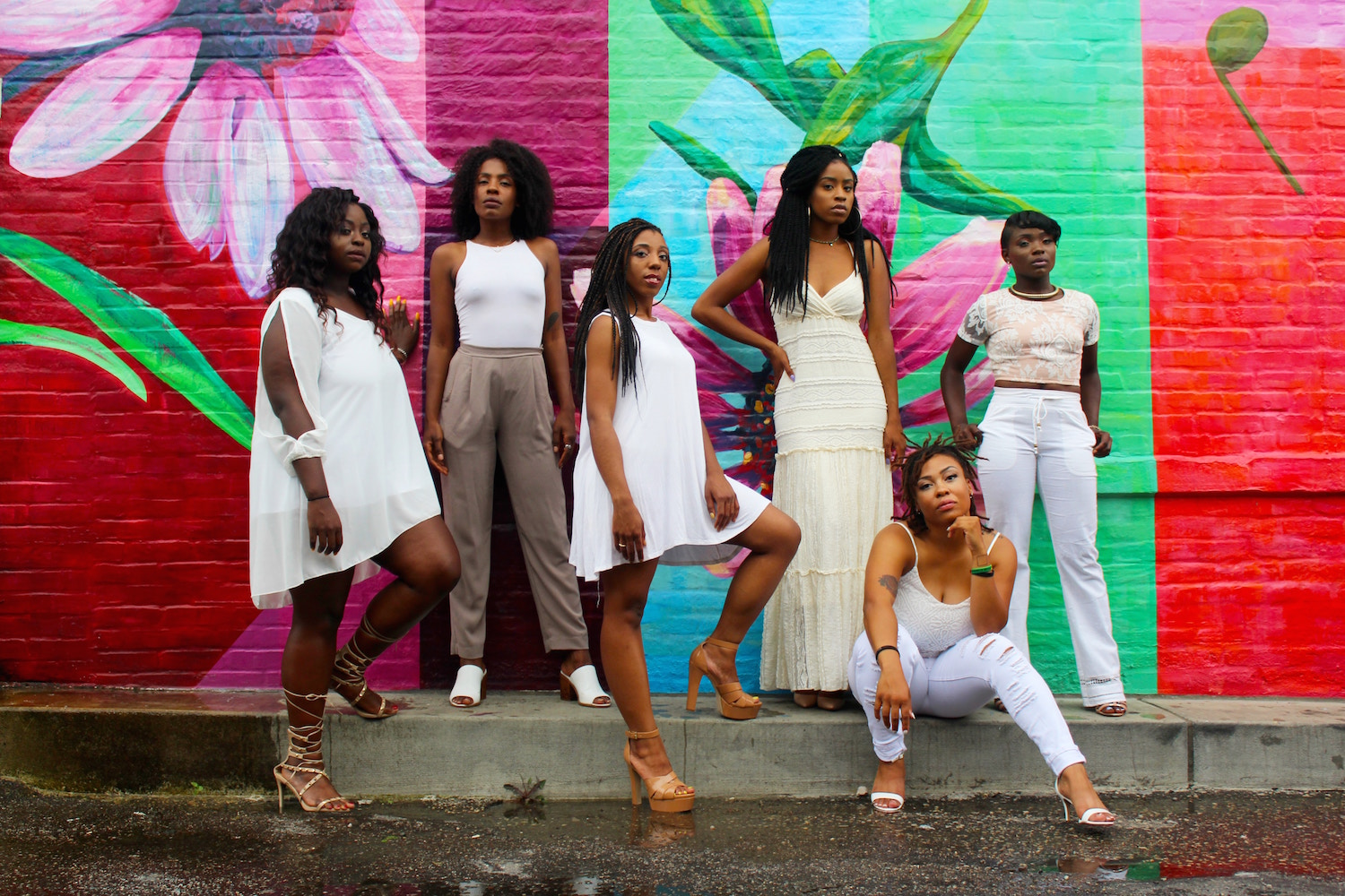 Black women dressed in white in front of a colorful mural