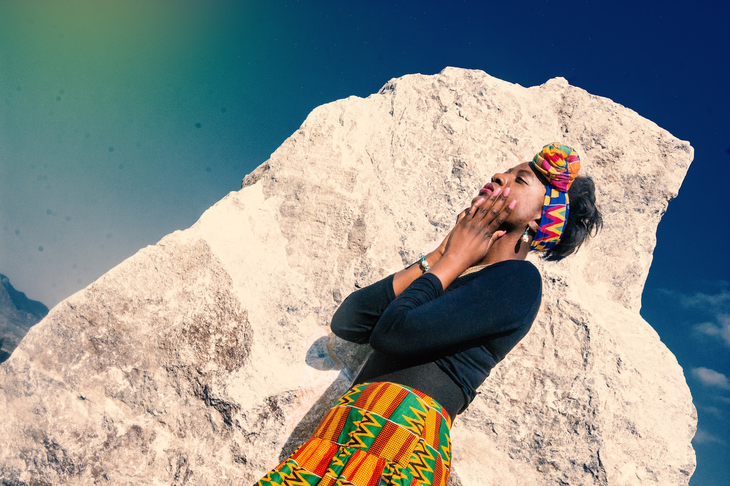 Black woman standing in front of a rock face