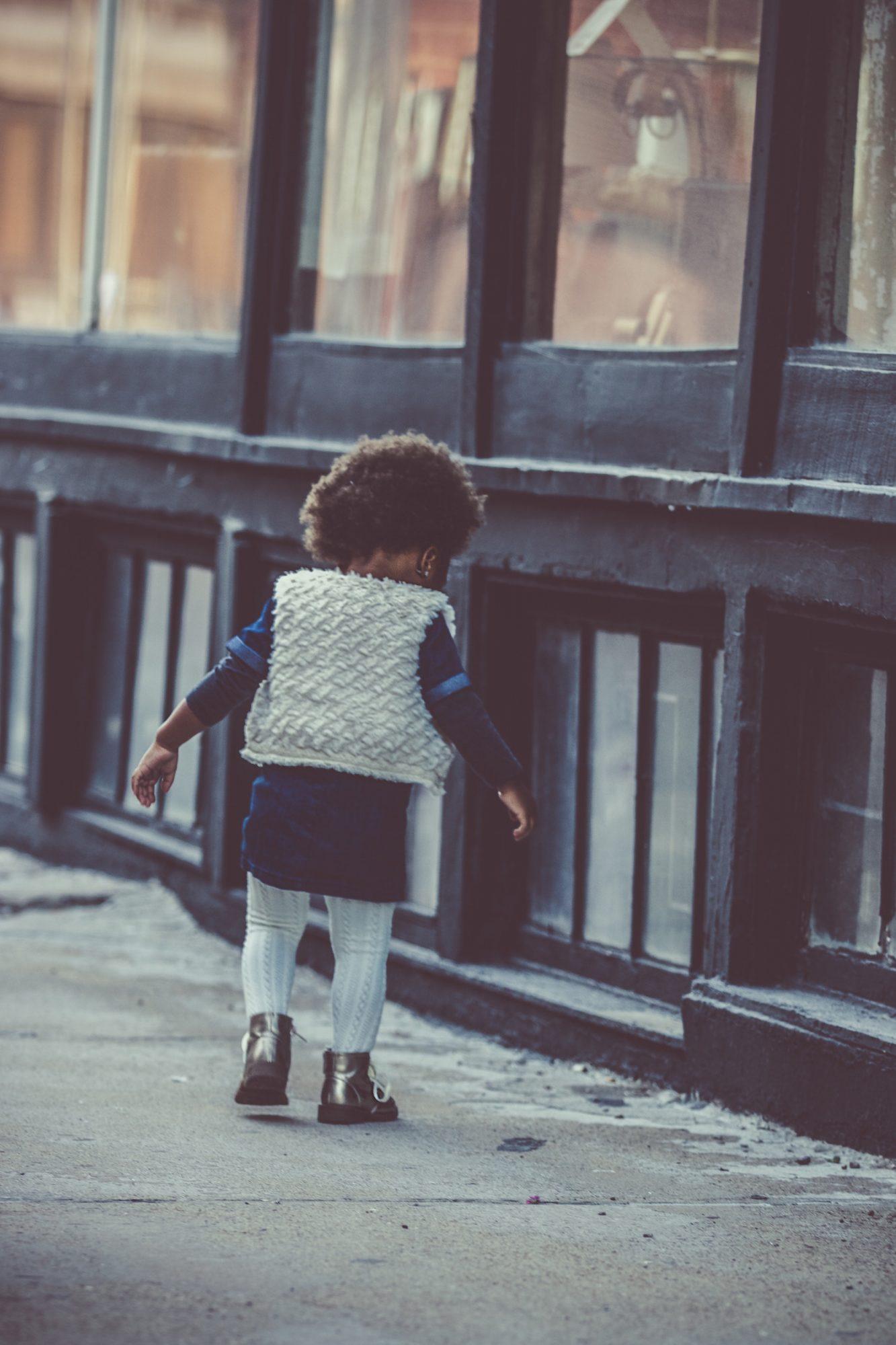 Young Black girl walking down the sidewalk