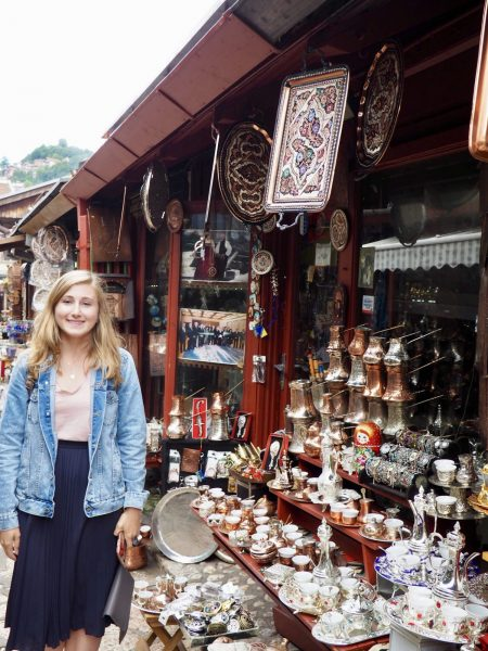 Woman standing in front of outdoor market stall with a bunch of trinkets