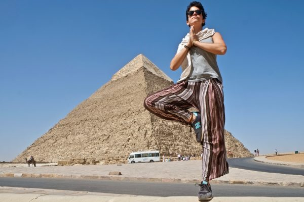 Woman doing a tree pose in front of the Pyramids of Giza