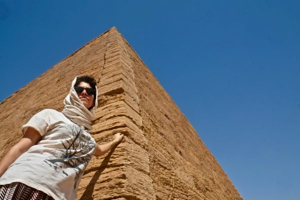 Woman with headscarf standing against a pyramid