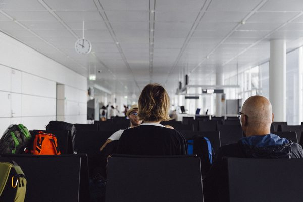 Two people sitting on seats in an airport lounge
