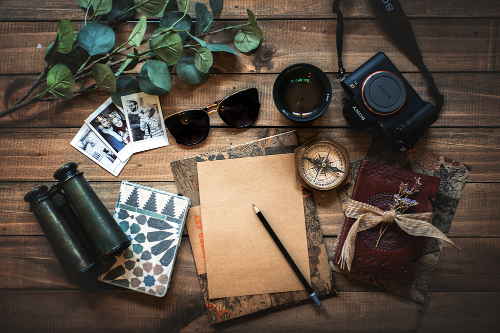 Flat lay of travel journal, notebooks, sunglasses, camera, binoculars, and others