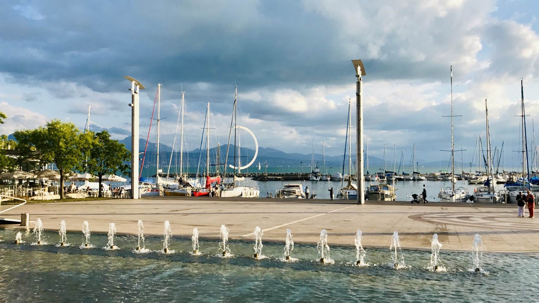 view of the harbor in Lausanne with boat masts and a fountain in the foreground