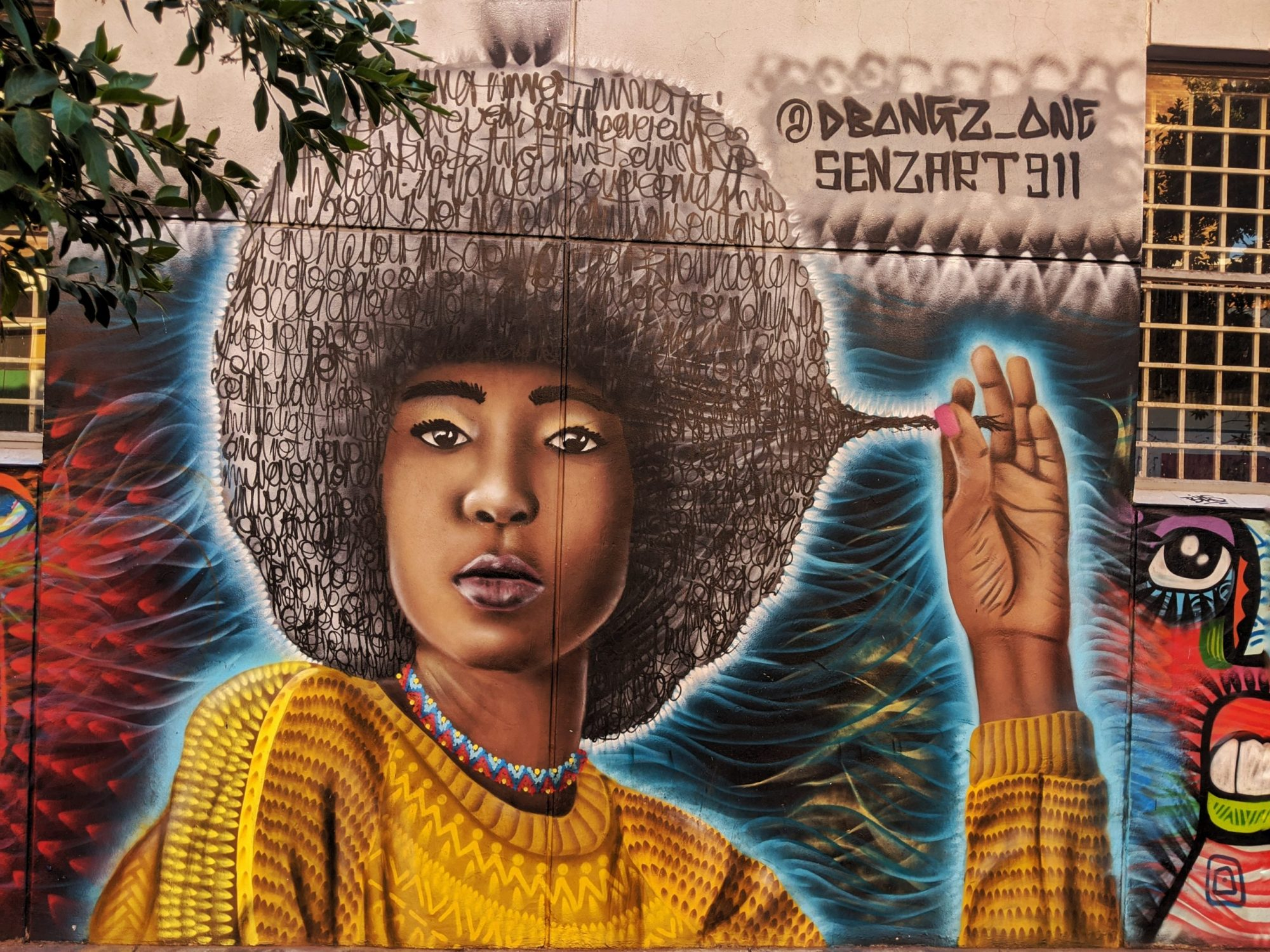 Street art portrait of a black woman with an afro in South Africa - unique destinations