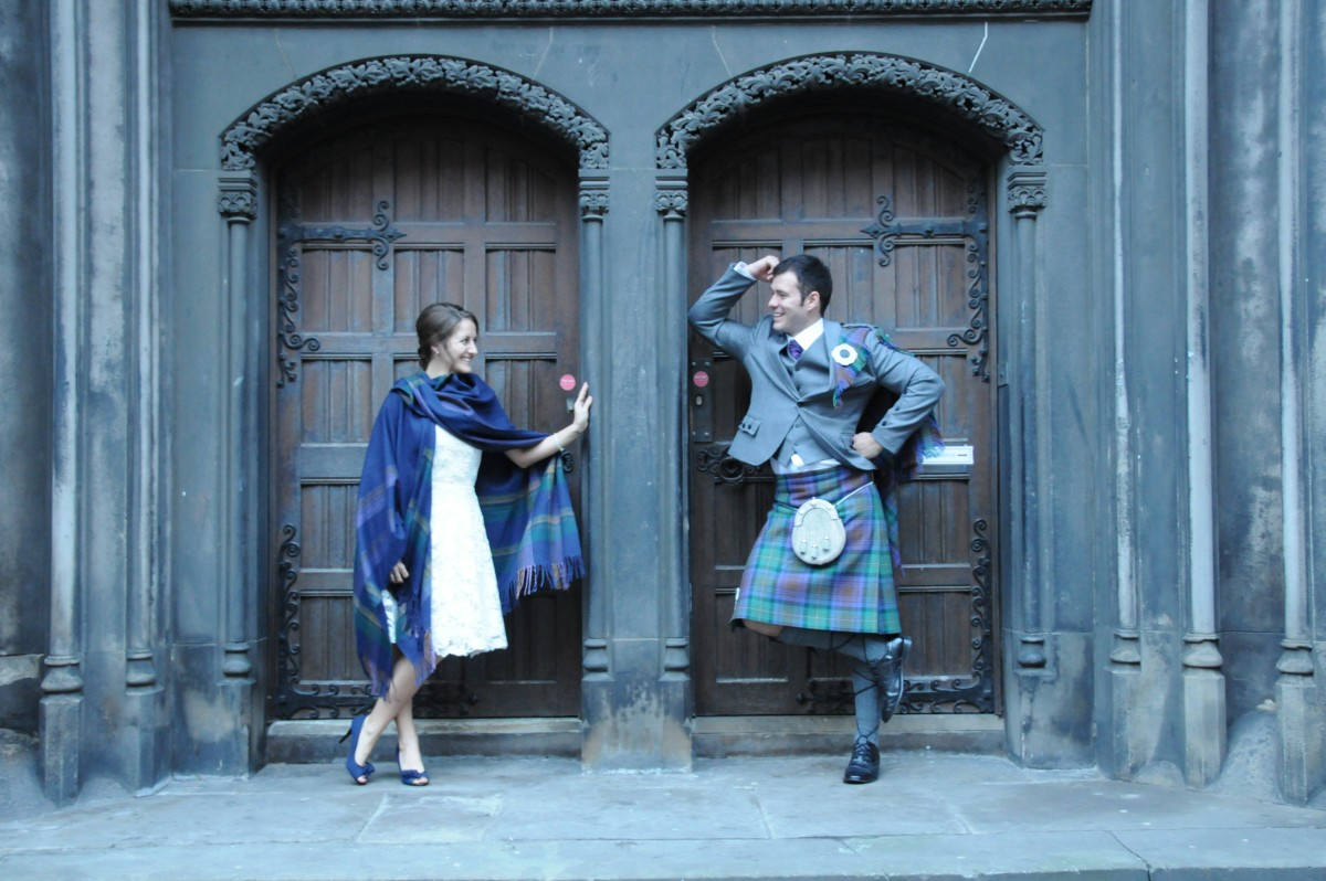 Amanda Walkins and husband posing on their wedding day in Edinburgh to share travel love stories on Wanderful