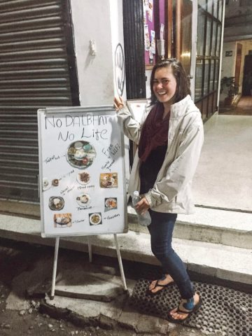 """Sarah Bence standing next to a sign that says """"no dal bhat no life"""""""