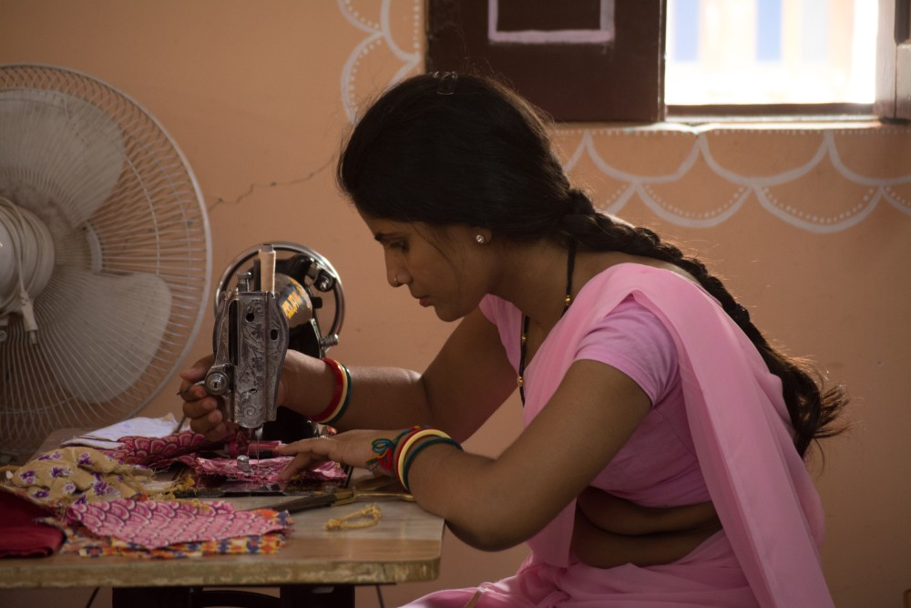 woman in a pink sari working on a sewing machine at the Sambhali Trust in Rajasthan during a Purposeful Nomad trip with Wanderful