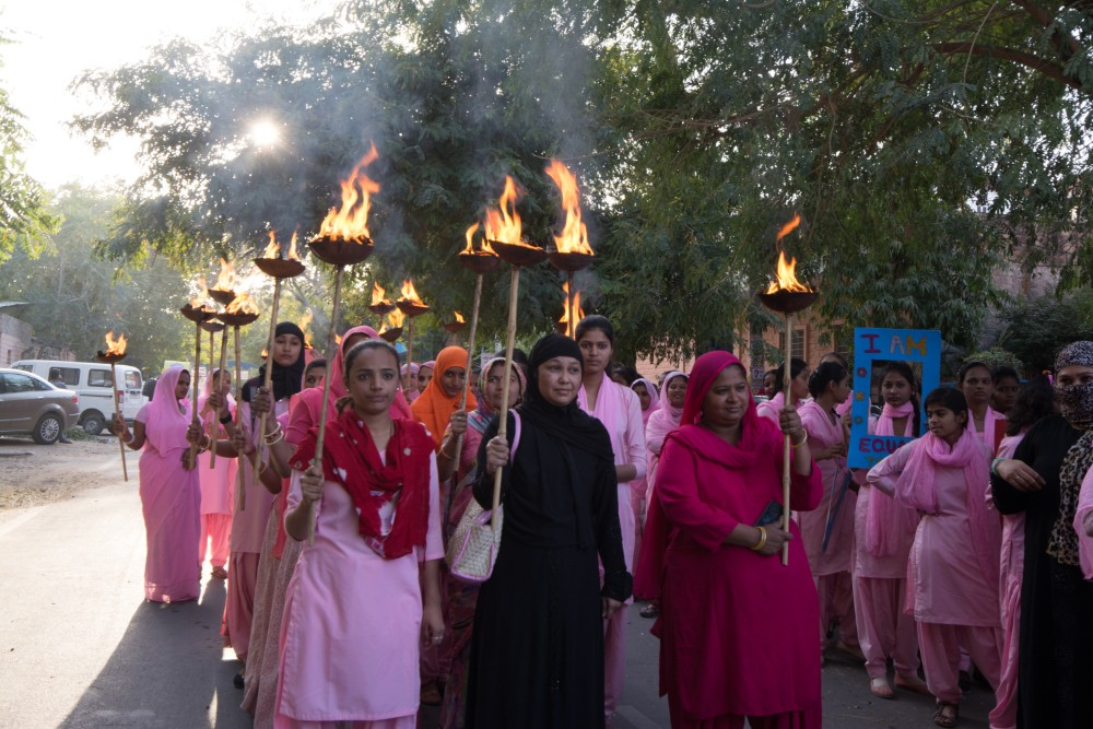 Women of Rajasthan in pink saris carrying torches for women's rights