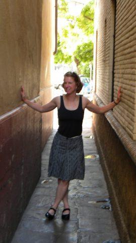 Health coach Becki Rupp standing in a narrow lane in Sevilla