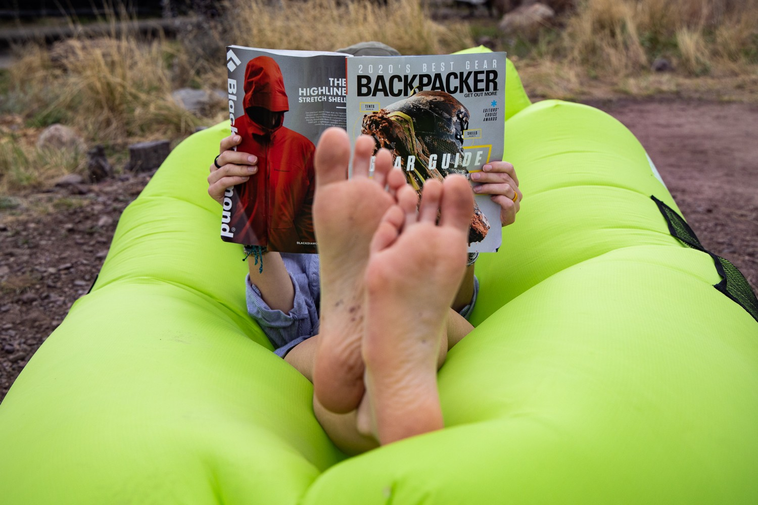 feet up relaxing on an inflatable while reading a magazine