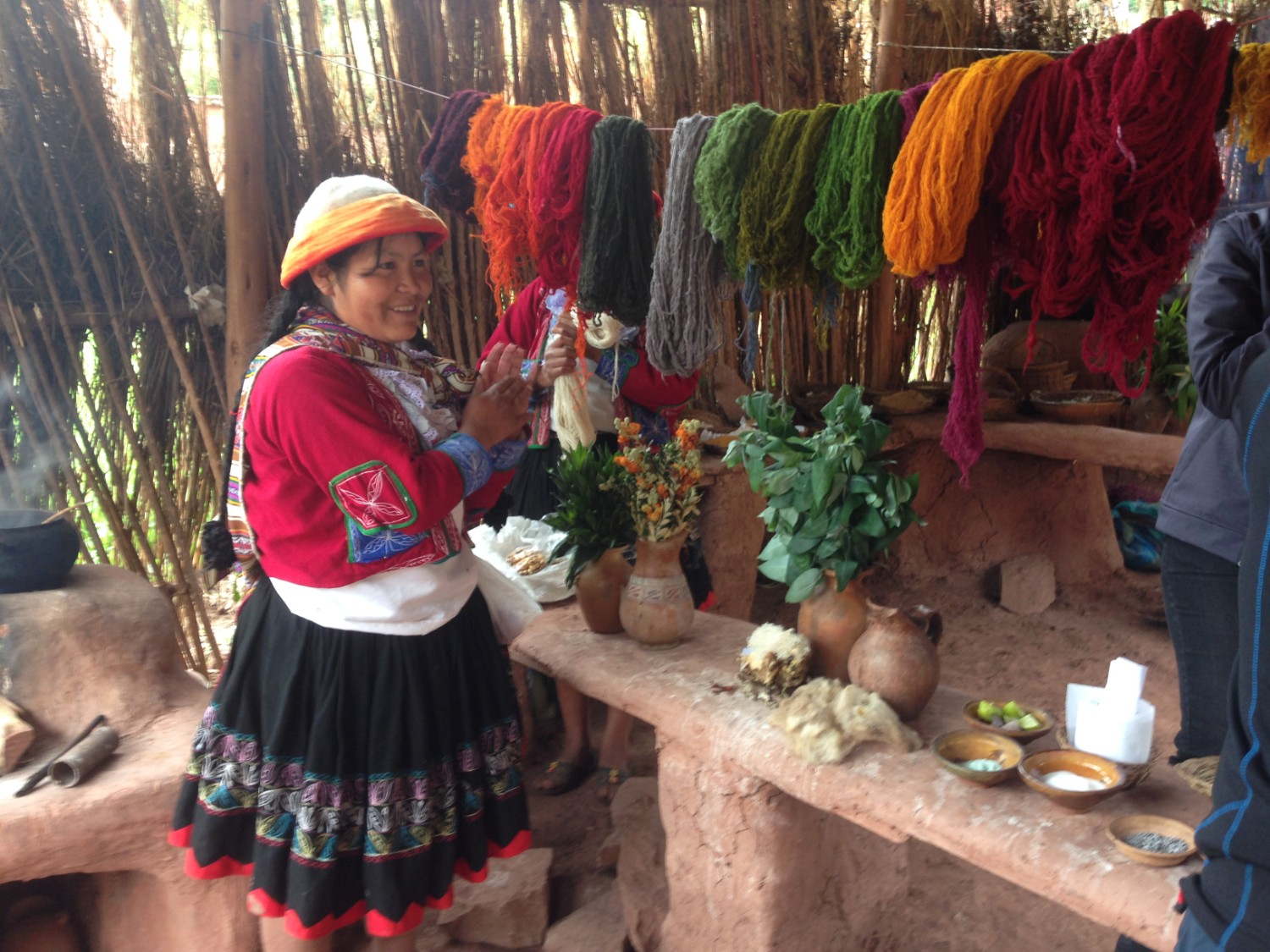 Woman in Ccaccaccollo standing next to dyed wool for the weaving cooperative