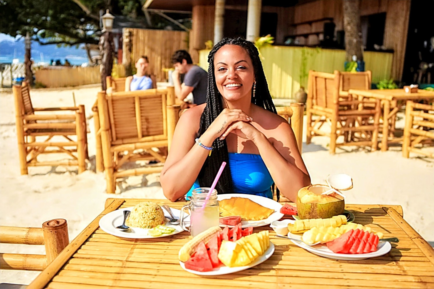 Karisma Shackelford of Wanderful sitting at a beach restaurant