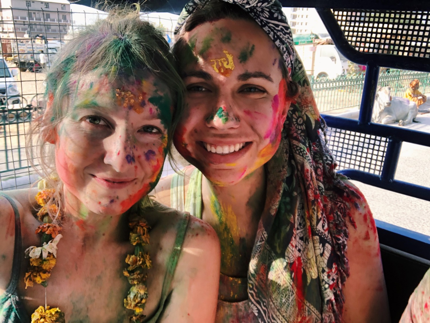 Two women covered in multicolors at Holi in India
