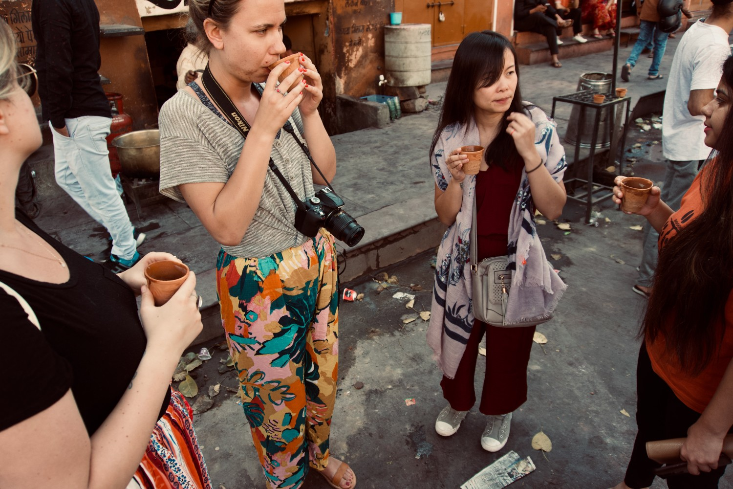 Origin Travels women's tour in India, women standing in a group tasting local drinks