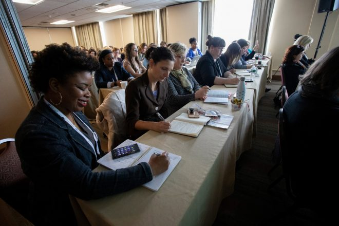 Women sitting at long conference tables taking notes at the Women in Travel Summit in Portland