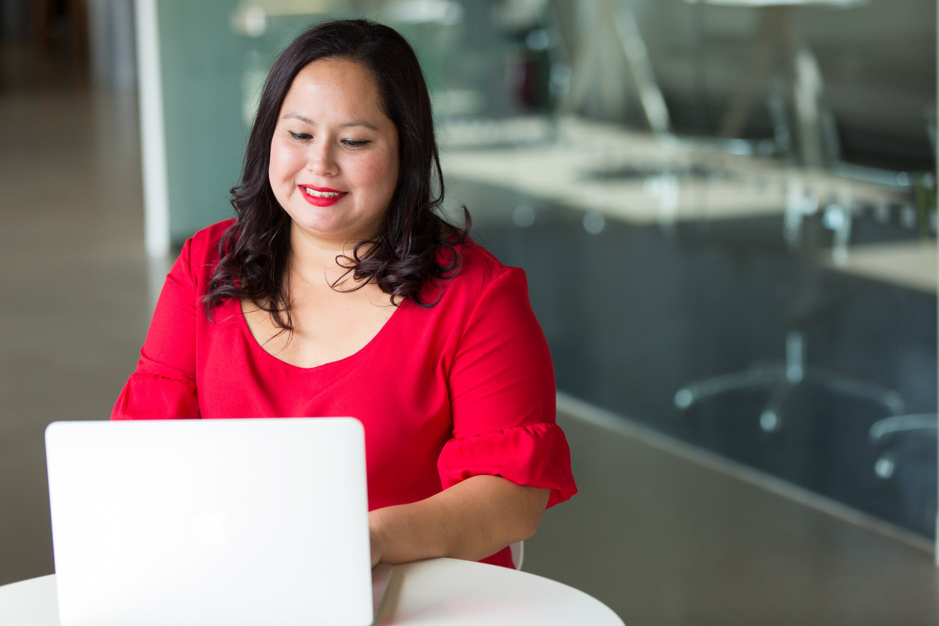 woman in a red shirt using a laptop