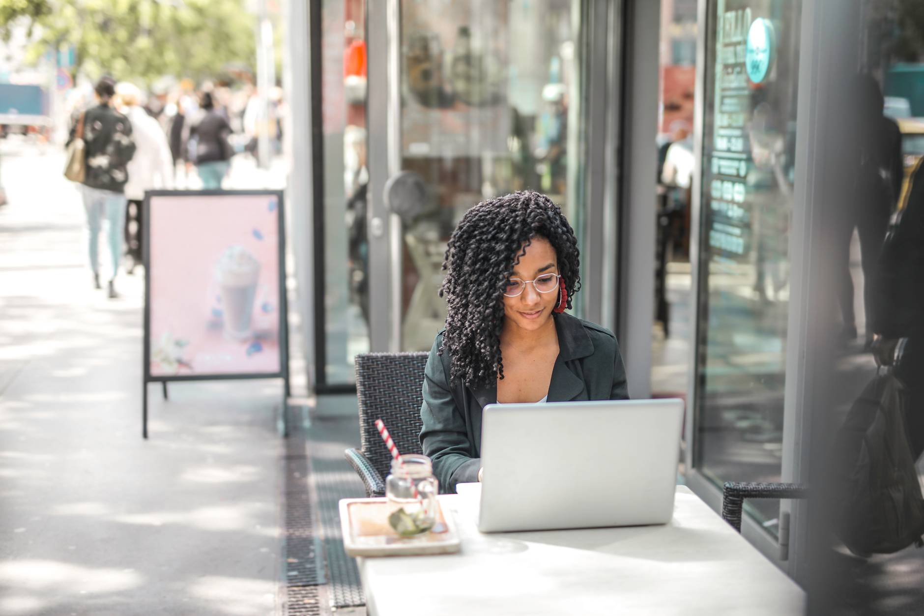 young woman using laptop while having tasty beverage in modern street cafe