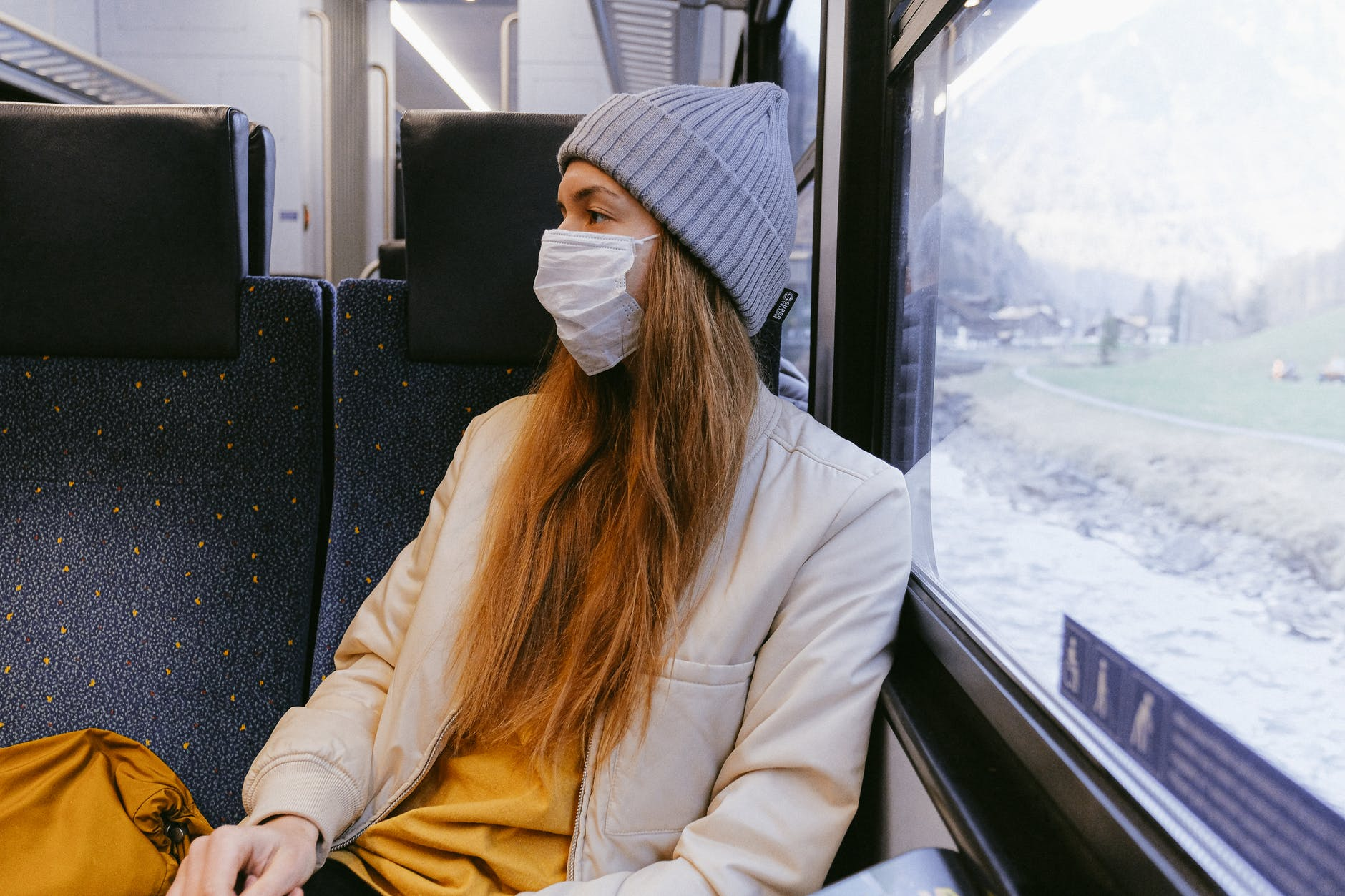 woman in gray knit cap and beige coat wearing a mask on a train