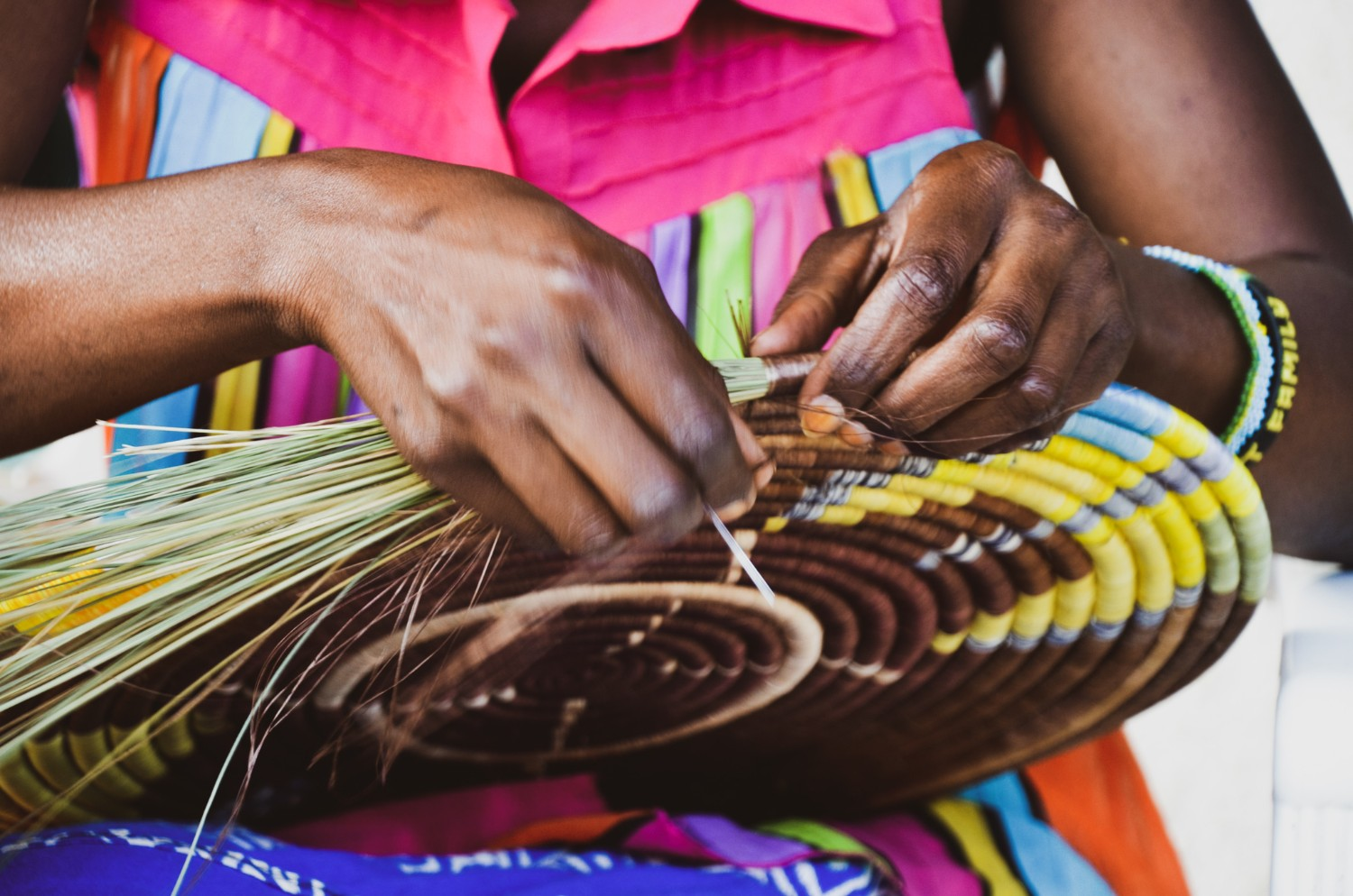 Close-up of a woman's hands as she weaves a traditional Rwandan peace basket
