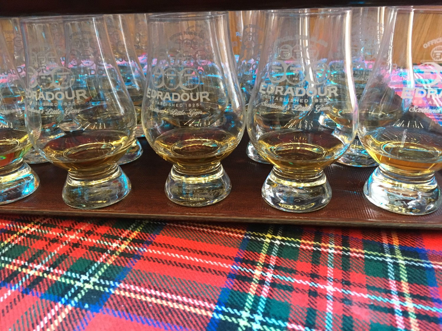 A tray full of drams of whisky resting on tartan at Edradour Distillery in Pitlochry, Scotland