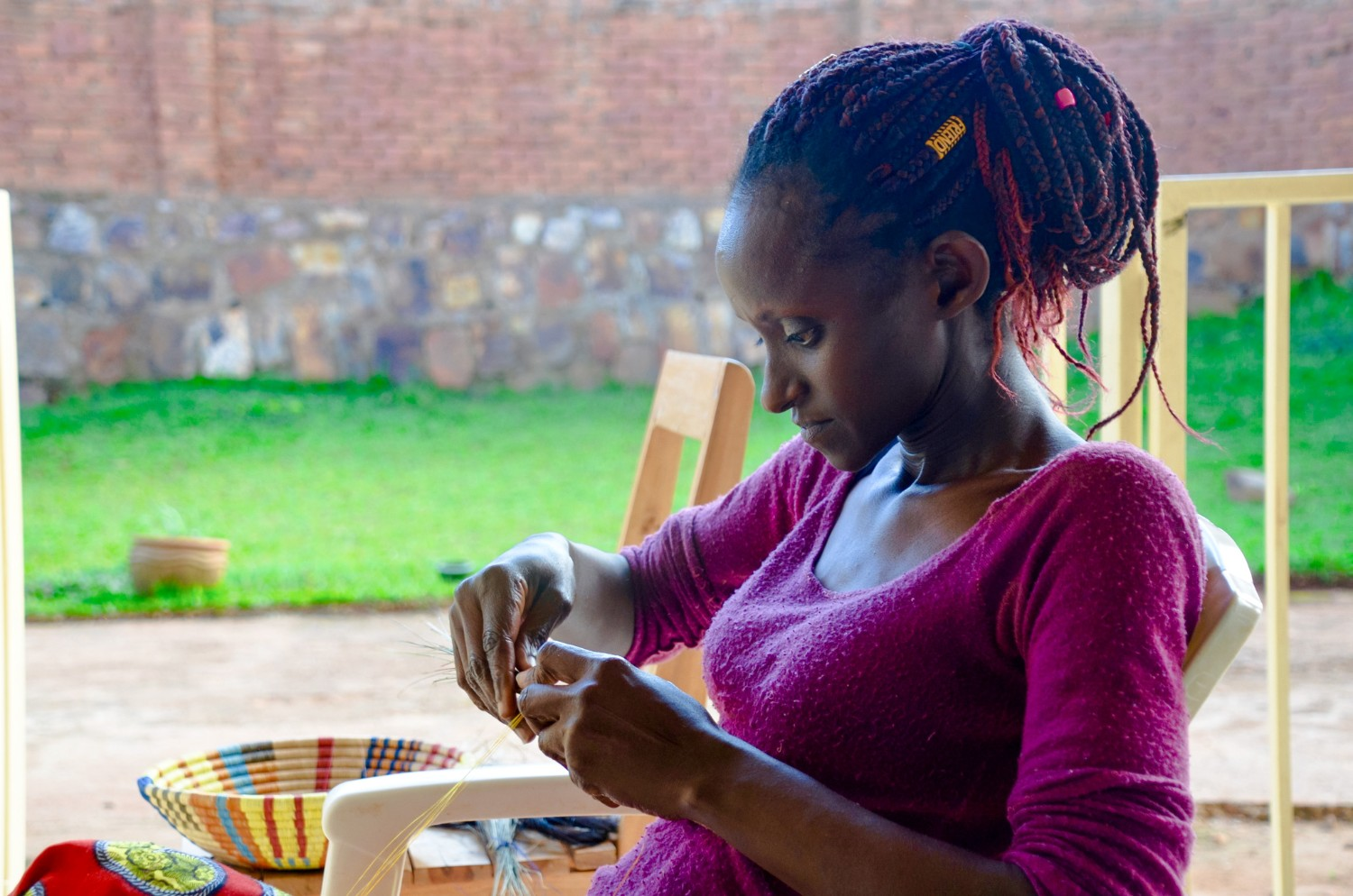 A Rwandese woman weaving a peace basket at Talking Through Art, a women's weaving cooperative