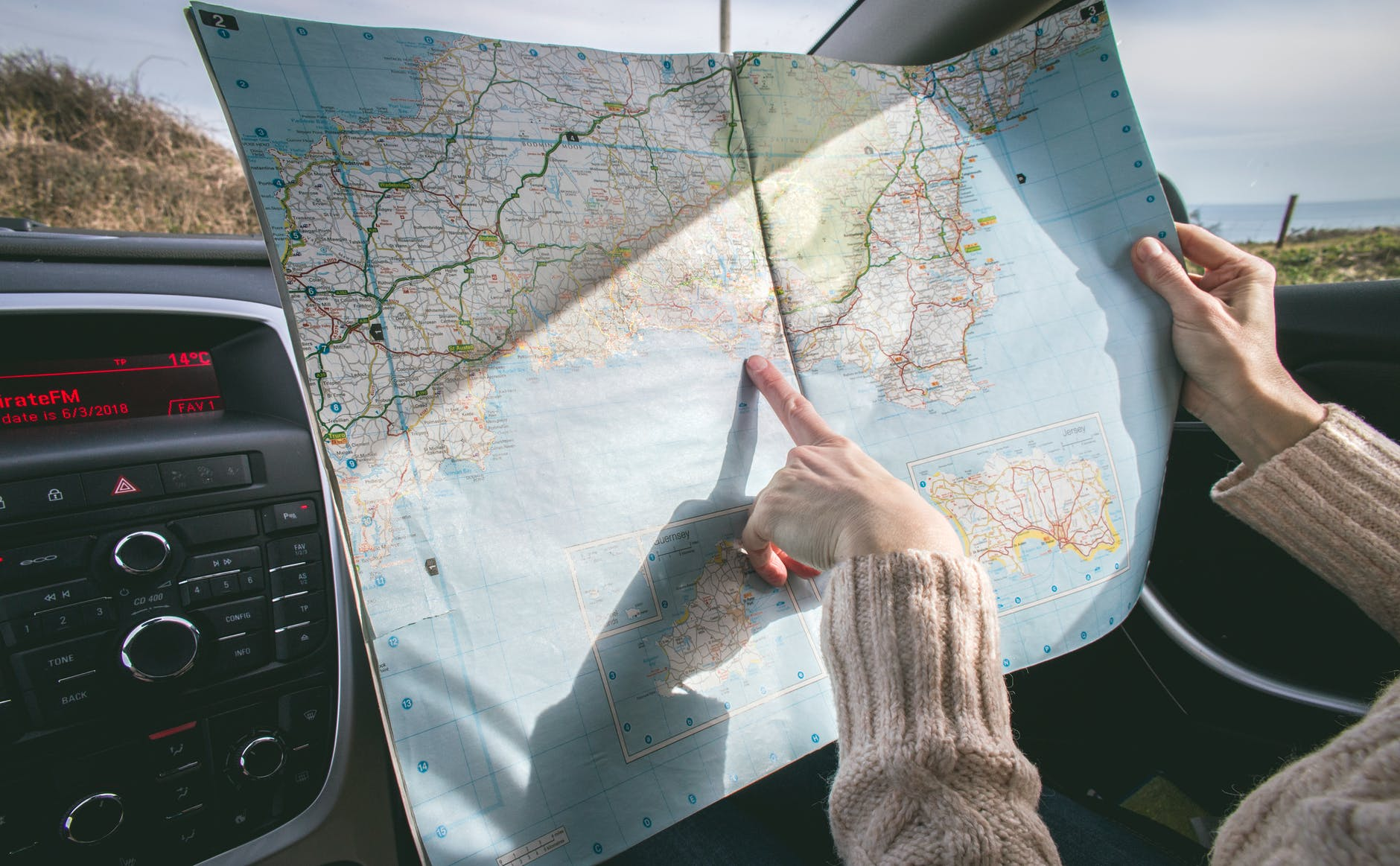 person wearing beige sweater holding map inside vehicle - solo road trips tips from travel experts via Wanderful
