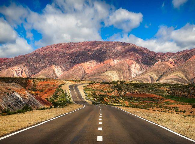 concrete road near brown mountain under blue sky