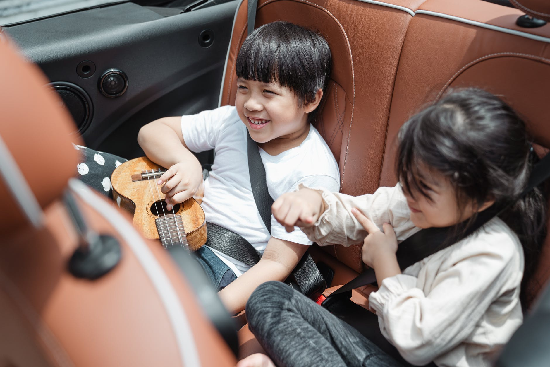 happy kids traveling in car - tips for road trips with family or friends