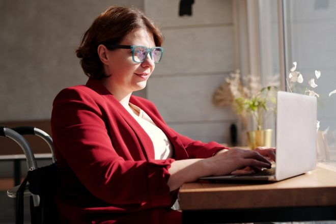 woman in a red blazer on a laptop - influencer marketing tips from Wanderful