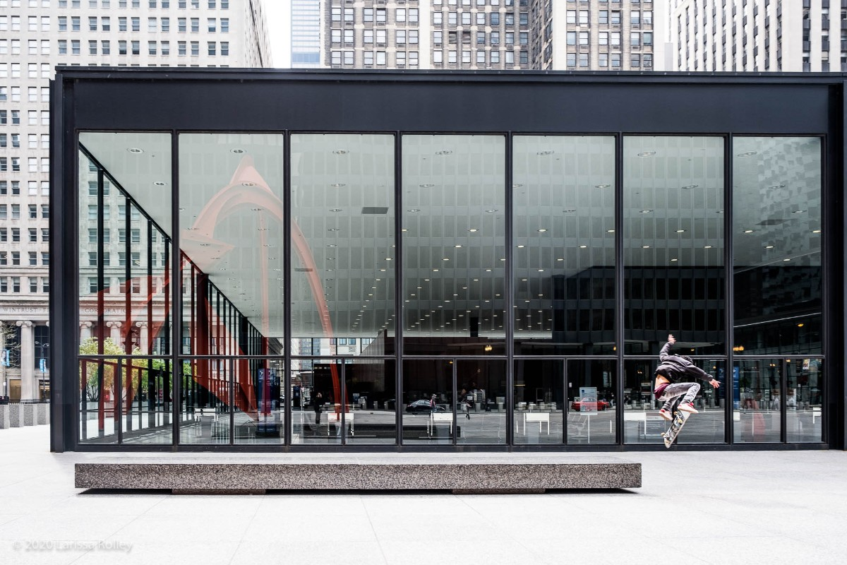 Skateboarder practicing jumps in front of large glass windows in a modern city building - photo by Larissa Rolley, photography course creator at Wanderful