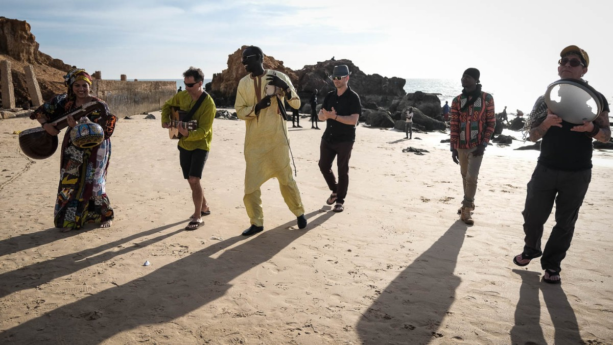 Group of people with long shadows playing music standing in the sand. Surabhi Ensemble in Senegal - photo by Larissa Rolley, photography course creator at Wanderful
