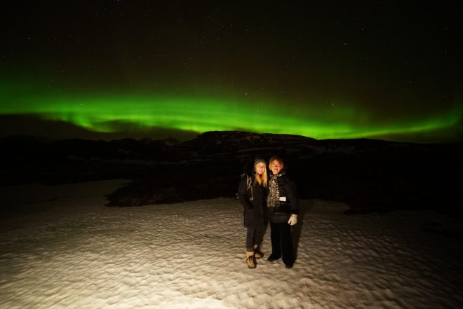 Northern Lights in Iceland with Laura Harris and her mom posing in front of a strong display