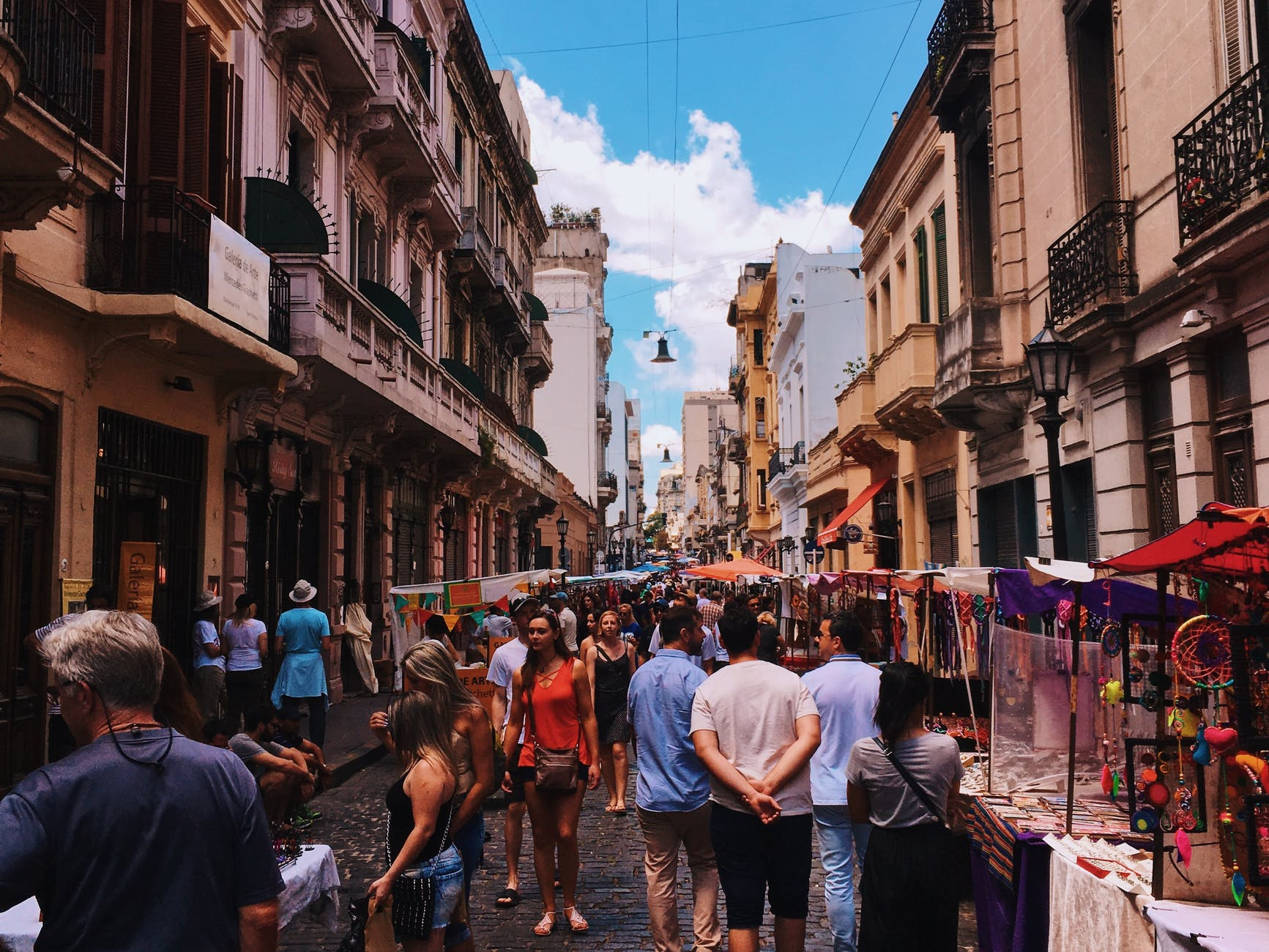 people standing on road beside market and high rise buildings - tips for planning a trip to Buenos Aires, Argentina, from Wanderful.