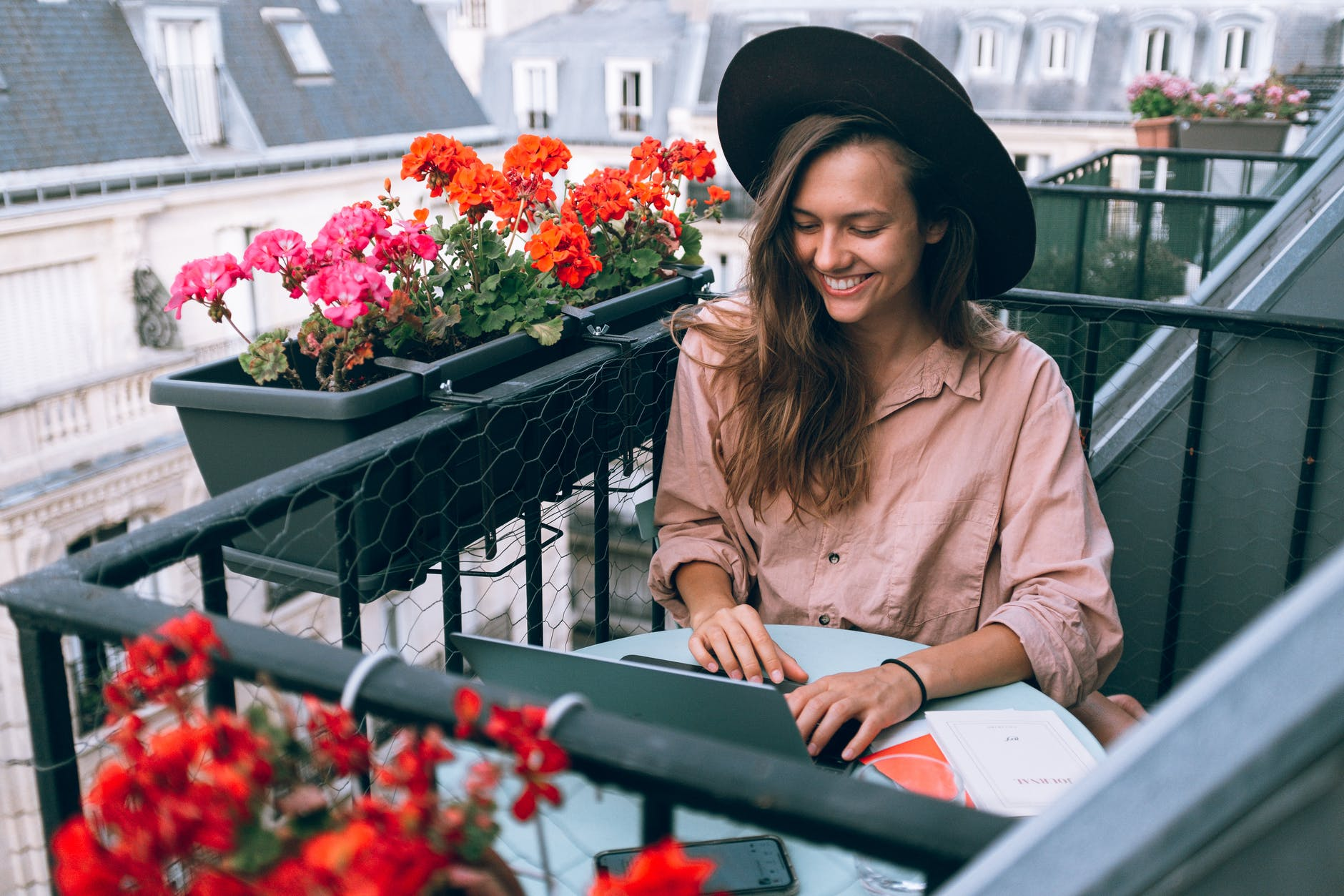 Woman using a laptop on a flower-filled balcony - learn SEO for Travel Bloggers and Businesses so you can work from anywhere and find success!