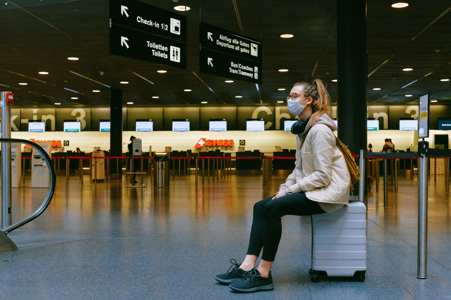Woman sitting on a rolling suitcase in an airport wearing a face mask to travel in this new world