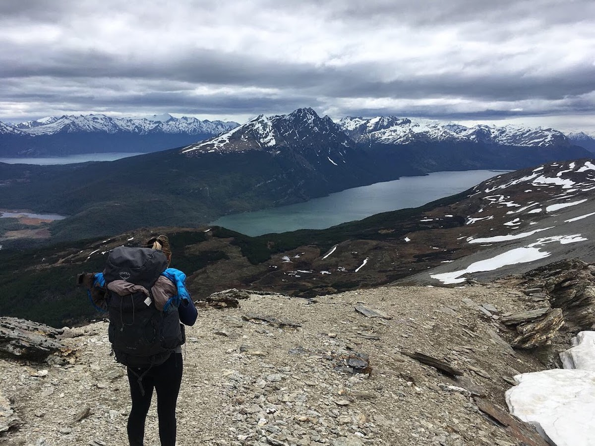 A hiker facing away from the camera with full pack on and overlooking a stunning mountain vistas with light snow dusting the peaks and lakes below. Taken at Cerro Guanaco inTierra del Fuego, Argentina, one of the best day hikes in Patagonia.