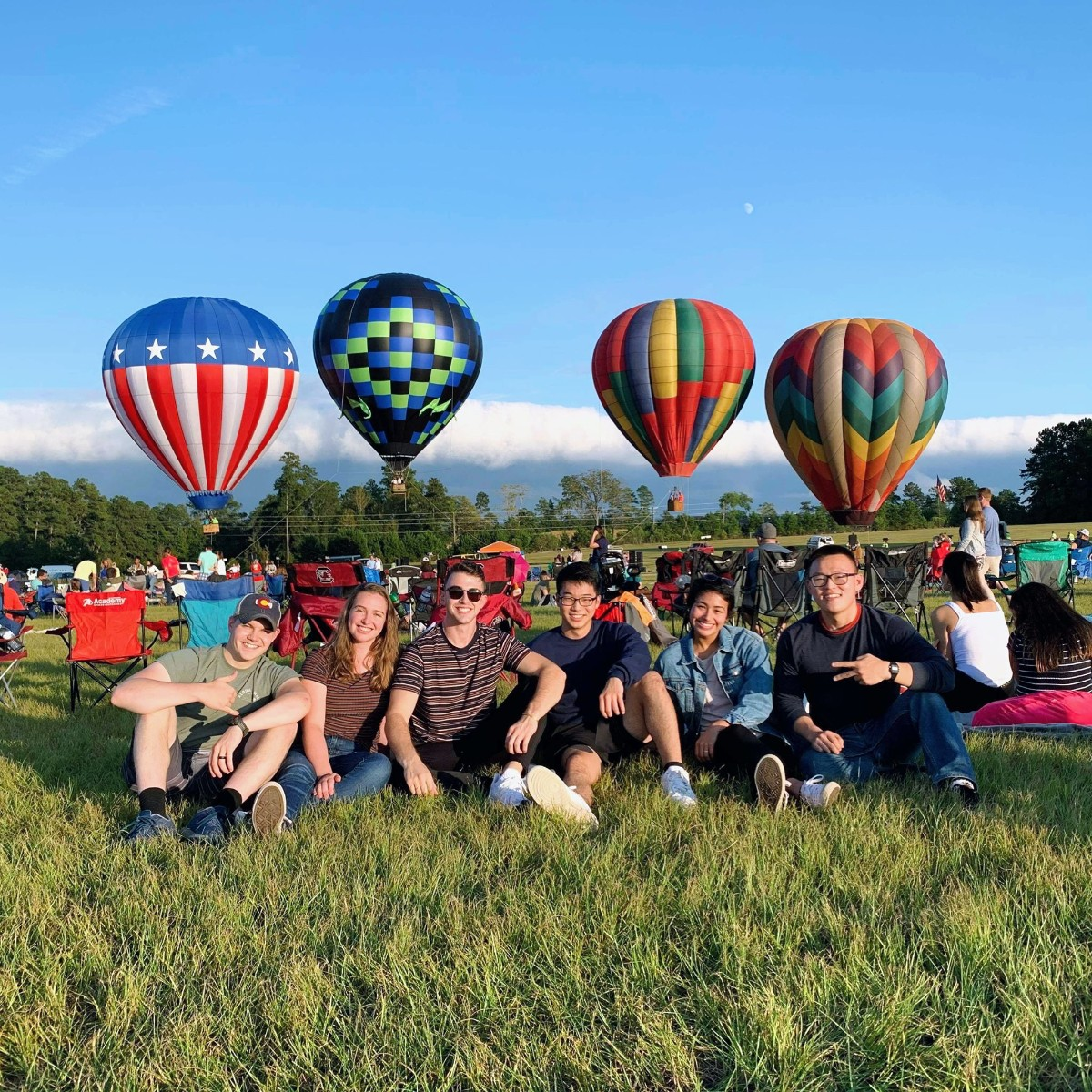 Group of friends sitting on a grassy hill with hot air balloons in the background
